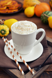 Pumpkin spice latte with whipped cream cinnamon and decorative pumpkins